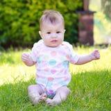 Ένα περίεργο μωρό σε μια συνεδρίαση φανέλλων στη χλόη στον κήπο Στοκ φωτογραφία με δικαίωμα ελεύθερης χρήσης