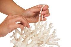 Ένα περιδέραιο μαργαριταριών στα χέρια της ενάντια στο σκηνικό του κοραλλιού Στοκ φωτογραφία με δικαίωμα ελεύθερης χρήσης