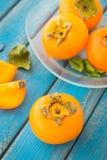 Ένα πιάτο γυαλιού persimmons γλυκών πορτοκαλιών Στοκ Εικόνες