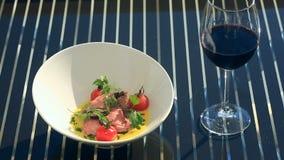 Ένα πιάτο ενός γαστρονομικού εστιατορίου Κινηματογράφηση σε πρώτο πλάνο Χοιρινό κρέας με τα λαχανικά και ένα ποτήρι του κόκκινου  απόθεμα βίντεο