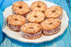 Ένα πιάτο με ένα μπισκότο κουλουρακιών και ένα φλυτζάνι του μαύρου τσαγιού με τα κομμάτια της ζάχαρης σε ένα μπλε ξύλινο υπόβαθρο Στοκ Φωτογραφία