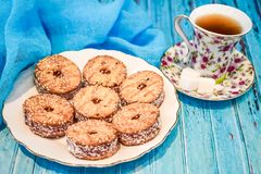 Ένα πιάτο με ένα μπισκότο κουλουρακιών και ένα φλυτζάνι του μαύρου τσαγιού με τα κομμάτια της ζάχαρης σε ένα μπλε ξύλινο υπόβαθρο Στοκ φωτογραφία με δικαίωμα ελεύθερης χρήσης