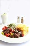 Ένα πιάτο με το ψημένα στη σχάρα συκώτι, το κρεμμύδι, τα λαχανικά, τις πατάτες και το ayran Στοκ φωτογραφία με δικαίωμα ελεύθερης χρήσης