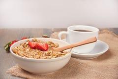 Ένα πιάτο με το muesli με τις φράουλες και το cuo του τσαγιού ή καφές στον ξύλινο πίνακα στοκ εικόνες