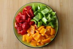 Ένα πιάτο που γεμίζουν με τα πιπέρια σε τρία χρώματα και την περικοπή στα τετράγωνα στοκ εικόνα με δικαίωμα ελεύθερης χρήσης