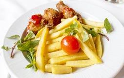 Ένα πιάτο του κοτόπουλου στο κόκκαλο στις τριμμένες φρυγανιές, που εξυπηρετείται με Frenc στοκ εικόνα