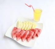 Ένα πιάτο του φρέσκων πεπονιού και του καρπουζιού με τη φυσική λεμονάδα Στοκ Εικόνες