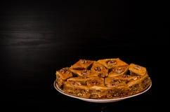Ένα πιάτο του baklava με το μέλι σε ένα μαύρο υπόβαθρο, παραδοσιακά τουρκικά γλυκά Rombus Στοκ εικόνα με δικαίωμα ελεύθερης χρήσης