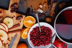 Ένα πιάτο των των βακκίνιων, δίπλα σε ένα τηγάνι με το θερμαμένο κρασί, μισά του πορτοκαλιού και φέτες των μήλων Στοκ εικόνες με δικαίωμα ελεύθερης χρήσης
