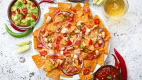 Ένα πιάτο των εύγευστων tortilla nachos με τη λειωμένη σάλτσα τυριών, ψημένο στη σχάρα κοτόπουλο φιλμ μικρού μήκους