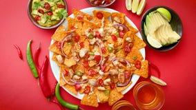 Ένα πιάτο των εύγευστων tortilla nachos με τη λειωμένη σάλτσα τυριών, ψημένο στη σχάρα κοτόπουλο απόθεμα βίντεο