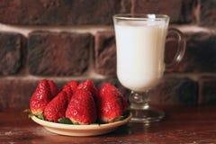 Ένα πιάτο των ώριμων φραουλών και μια κούπα του γάλακτος για το πρόγευμα στοκ φωτογραφία με δικαίωμα ελεύθερης χρήσης