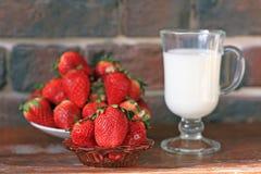 Ένα πιάτο των ώριμων φραουλών και μια κούπα του γάλακτος για το πρόγευμα στοκ φωτογραφίες με δικαίωμα ελεύθερης χρήσης