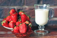 Ένα πιάτο των ώριμων φραουλών και μια κούπα του γάλακτος στοκ εικόνα