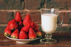 Ένα πιάτο των ώριμων φραουλών και μια κούπα του γάλακτος στοκ εικόνες
