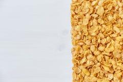 Ένα πλαίσιο που ευθυγραμμίζεται με τις νιφάδες καλαμποκιού Δημητριακά που διασκορπίζονται σε έναν ξύλινο πίνακα Στοκ Εικόνα