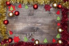 Ένα πλαίσιο Χριστουγέννων που διακοσμείται με τις γιρλάντες, τις σφαίρες Χριστουγέννων και το δ Στοκ Εικόνες