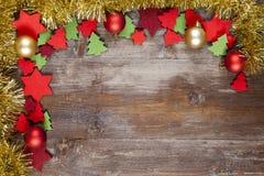 Ένα πλαίσιο Χριστουγέννων που διακοσμείται με τις χρυσές γιρλάντες, σφαίρα Χριστουγέννων Στοκ Φωτογραφία