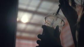 Ένα πλαστικό φλυτζάνι με ένα άχυρο στα χέρια θηλυκών απόθεμα βίντεο