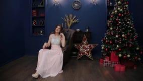Ένα πολύ όμορφο κορίτσι κάθεται σε μια καρέκλα δέρματος στο ντεκόρ του νέου έτους απόθεμα βίντεο