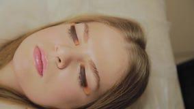 Ένα πολύ όμορφο κορίτσι σε ένα σαλόνι ομορφιάς κάνει μια ελασματοποίηση μαστιγώνει Αναμονή την κόλλα στα eyelashes που ξεραίνουν απόθεμα βίντεο