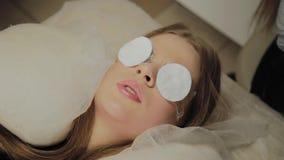 Ένα πολύ όμορφο κορίτσι σε ένα σαλόνι ομορφιάς κάνει μια ελασματοποίηση μαστιγώνει Αναμονή την κόλλα στα eyelashes που ξεραίνουν φιλμ μικρού μήκους