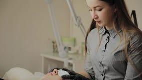 Ένα πολύ όμορφο κορίτσι σε ένα σαλόνι ομορφιάς κάνει μια ελασματοποίηση μαστιγώνει Το Beautician διορθώνει τους δίσκους βαμβακιού απόθεμα βίντεο
