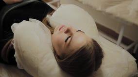 Ένα πολύ όμορφο κορίτσι σε ένα σαλόνι ομορφιάς κάνει μια ελασματοποίηση μαστιγώνει Να βρεθεί αναμένοντας το ξεραίνοντας χρώμα στα απόθεμα βίντεο