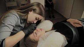 Ένα πολύ όμορφο κορίτσι σε ένα σαλόνι ομορφιάς κάνει μια ελασματοποίηση μαστιγώνει Το Beautician εκτελεί τη διαδικασία eyelash φιλμ μικρού μήκους