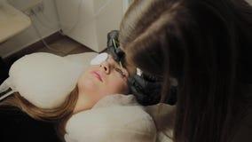 Ένα πολύ όμορφο κορίτσι σε ένα σαλόνι ομορφιάς κάνει μια ελασματοποίηση μαστιγώνει Το Beautician εκτελεί τη διαδικασία eyelash απόθεμα βίντεο