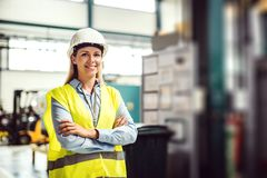 Ένα πορτρέτο ενός βιομηχανικού μηχανικού γυναικών που στέκεται σε ένα εργοστάσιο, όπλα που διασχίζονται στοκ φωτογραφία