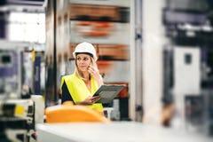 Ένα πορτρέτο ενός βιομηχανικού μηχανικού γυναικών στο τηλέφωνο, που στέκεται σε ένα εργοστάσιο στοκ φωτογραφία με δικαίωμα ελεύθερης χρήσης