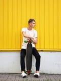 Ένα πορτρέτο ενός κοριτσιού hipster με τη σκοτεινή τρίχα στα περιστασιακά ενδύματα που θέτουν σε ένα κίτρινο υπόβαθρο τοίχων Μοντ στοκ εικόνες με δικαίωμα ελεύθερης χρήσης
