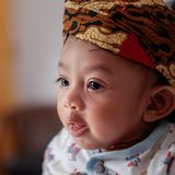 Ένα πορτρέτο ενός 3 μηνών μωρού που παρουσιάζει ένα χαμόγελο και που φορά Blangkon Το Blangkon είναι μια χαρακτηριστική επικεφαλή στοκ εικόνες με δικαίωμα ελεύθερης χρήσης