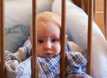 Ένα πορτρέτο ενός μικρού αγοριού που βρίσκεται σε ένα παιχνίδι παχνιών στοκ εικόνες