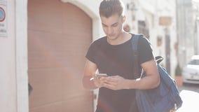 Ένα πορτρέτο ενός όμορφου smartphone σερφ νεαρών άνδρων και περπάτημα για την πόλη ανασκόπηση ηλιόλουστη ανασκόπηση που θολώνεται φιλμ μικρού μήκους