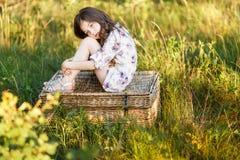 Ένα πορτρέτο μιας λυπημένης χαριτωμένης δυτικής συνεδρίασης μικρών κοριτσιών σε ένα καλάθι έξω στο ηλιοβασίλεμα στοκ φωτογραφία με δικαίωμα ελεύθερης χρήσης