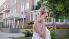 Ένα πορτρέτο μιας χαμογελώντας όμορφης γυναίκας στο άσπρο φόρεμα που μιλά στο τηλέφωνο με το φίλο της σε θερινή περίοδο απόθεμα βίντεο