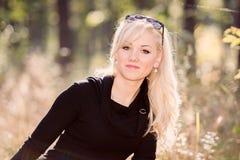Ένα πορτρέτο νέων, ξανθών και γυναικών χαμόγελου μια ηλιόλουστη ημέρα φθινοπώρου Στοκ φωτογραφία με δικαίωμα ελεύθερης χρήσης