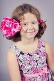 Όμορφο κορίτσι με ένα ρόδινο λουλούδι στην τρίχα της Στοκ Φωτογραφία