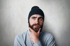 Ένα πορτρέτο στούντιο του μοντέρνου ατόμου με την παχιά μαύρη γενειάδα που φορά τη μαύρη ΚΑΠ και το περιστασιακό ελεγχμένο πουκάμ στοκ φωτογραφίες με δικαίωμα ελεύθερης χρήσης
