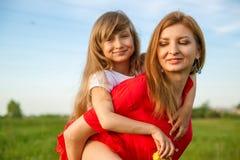 Ένα πορτρέτο της ευτυχών μητέρας και της κόρης στον πράσινο τομέα στη φύση το καλοκαίρι Φύση, ευτυχία στοκ εικόνα