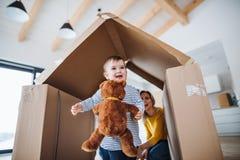 Ένα πορτρέτο της νέας οικογένειας με ένα κορίτσι μικρών παιδιών, που κινείται στη νέα εγχώρια έννοια στοκ φωτογραφία με δικαίωμα ελεύθερης χρήσης