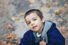 Ένα πορτρέτο του λίγο όμορφου χαμογελώντας αγοριού στο δρόμο στο δάσος φθινοπώρου στοκ φωτογραφία με δικαίωμα ελεύθερης χρήσης