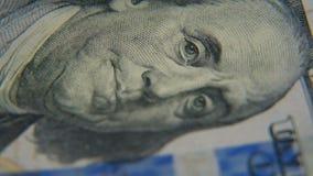 Ένα πορτρέτο του Benjamin Franklin σε μια κινηματογράφηση σε πρώτο πλάνο λογαριασμών εκατό-δολαρίων φιλμ μικρού μήκους
