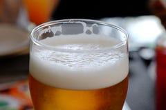 Ένα ποτήρι της κρύας μπύρας με την κινηματογράφηση σε πρώτο πλάνο αφρού στοκ εικόνες