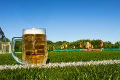 Ένα ποτήρι της μπύρας είναι σε έναν αγωνιστικό χώρο ποδοσφαίρου, το ποδόσφαιρο παίζεται στο στάδιο στοκ εικόνες
