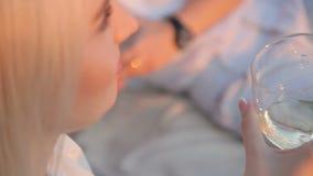 Ένα ποτήρι της σαμπάνιας στα χέρια ενός κοριτσιού φιλμ μικρού μήκους