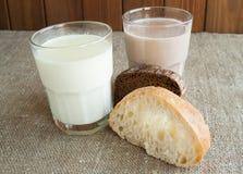 Ένα ποτήρι του γάλακτος και ένα ποτήρι του κακάου με τα κομμάτια του σπιτικού ψωμιού Στοκ Εικόνες
