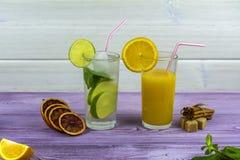 Ένα ποτήρι του γλυκού συμπίεσε πρόσφατα το χυμό από πορτοκάλι και ένα γυαλί Mojito με τον πάγο Κλαδάκι της μέντας και των πορτοκα στοκ φωτογραφίες